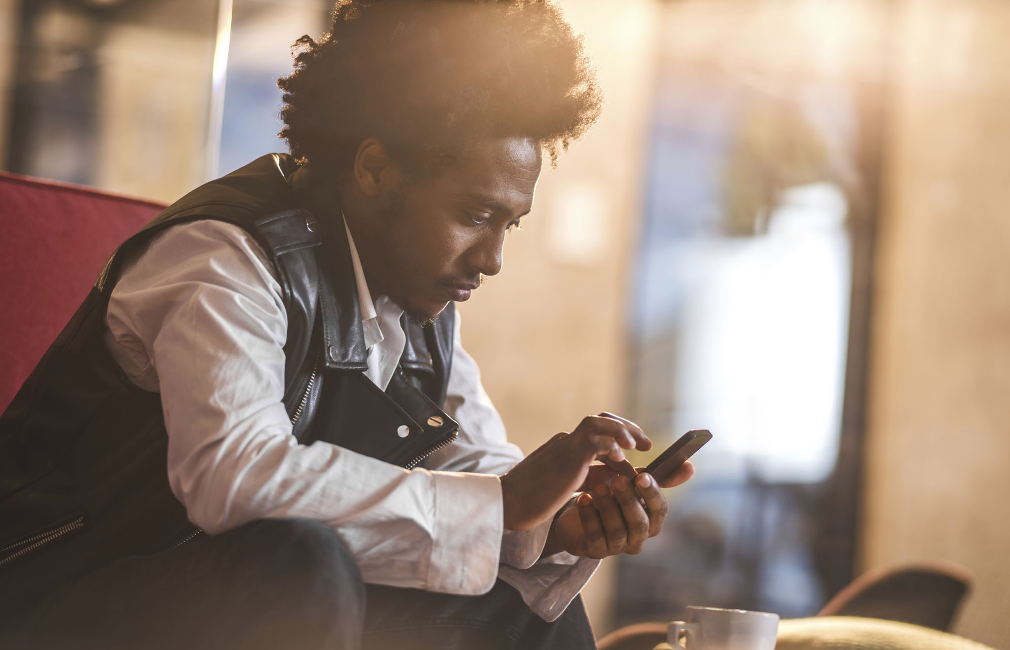 Pensive African American young man using mobile phone on a coffee break and text messaging.